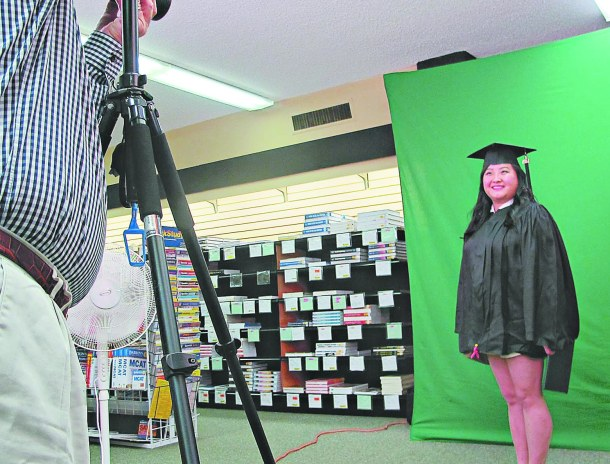 BILLY HUDSPETH/THE ARKA TECH: Gao Xiong receives her graduation portrait, taken by Joey Fasullo of Candid Campus Photography, during Arkansas Tech's Grad Fair on Oct. 8 and 9.