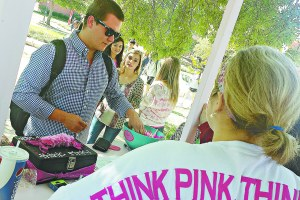 "SHANE CRABTREE/THE ARKA TECH: James Bond, a senior mechanical engineering major from Bentonville, picks three Hershey's Kisses from a bowl after donating $1 to the Zeta Tau Alpha Kissing Booth on Monday. The Kissing Booth was created by ZTA as part of the sorority's ""Think Pink"" month, which raises public awareness of breast cancer."