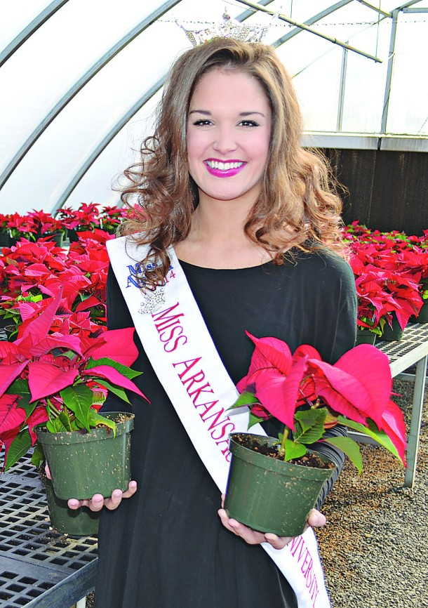 TOMMY MUMERT/THE ARKA TECH: Logan Moore, a sophomore nursing major from Van Buren and the reigning Miss Arkansas Tech, poses with two of the many poinsettias that will be for sale Dec. 4 and 5 during the agriculture department's annual sale. All proceeds from the sale remain with the department for greenhouse plants and supplies. The sale will be held from 8 a.m. to 5 p.m. both days at the greenhouses on Red Hill Farm.
