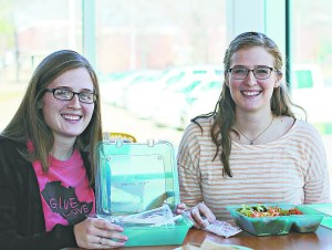 CLAUDIA HALL/THE ARKATECH: Emily and Lindsay Walters, senior vocal music majors from Harrison, enjoy using the new takeout containers provided by the cafeteria.